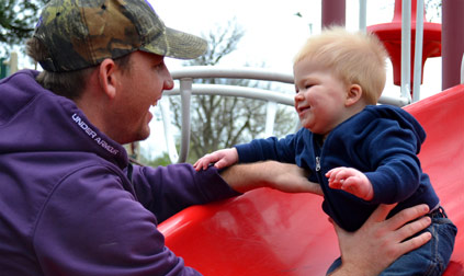 Man in a purple jacket and a baby play at the playground.